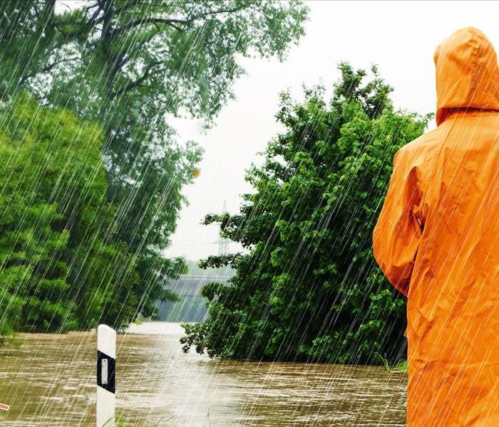 person in orange rain jacket standing in front of flooded road